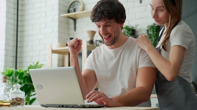 Casal animado com laptop na cozinha comemorando o sucesso