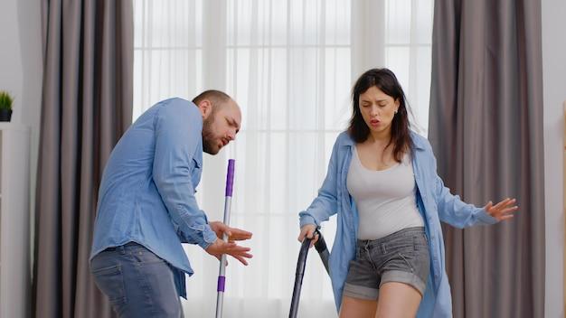 Casal animado dançando enquanto limpa a casa usando esfregão e aspirador de pó