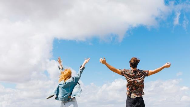Casal animado e livre com as mãos para cima
