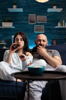 Casal animado e relaxado assistindo tv no sofá e relaxando tarde da noite