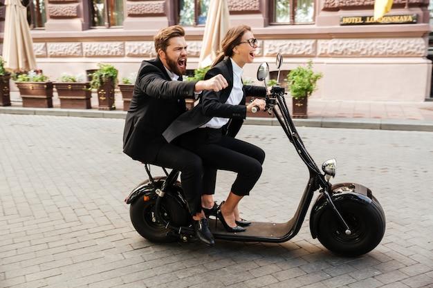 Casal animado feliz vestindo roupas inteligentes, andar de bicicleta a motor