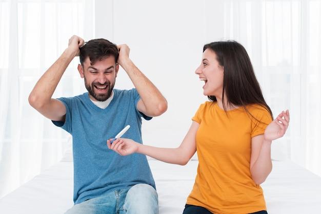 Casal animado segurando o teste de gravidez