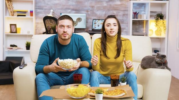 Casal animado sentado no sofá comendo junk food e torcendo por seu time de esporte enquanto assiste tv. gato sentado no sofá.