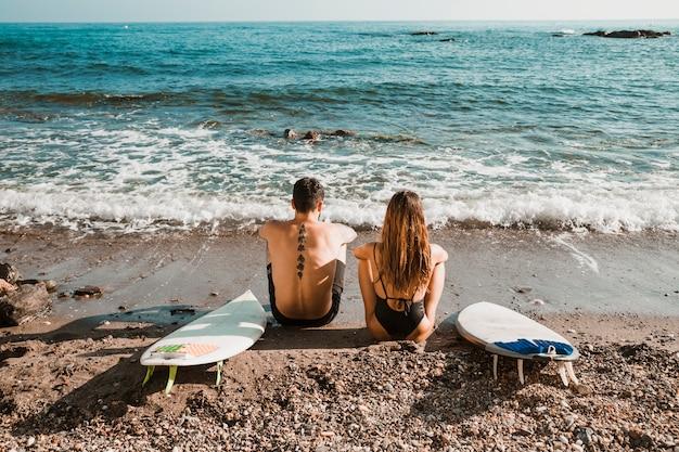 Casal anônimo com pranchas olhando para acenar do mar