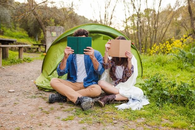 Casal anônimo lendo livros perto da tenda