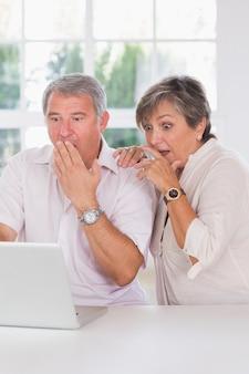 Casal antigo chocado diante de um laptop