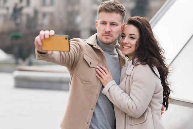 Casal ao ar livre tomando uma selfie