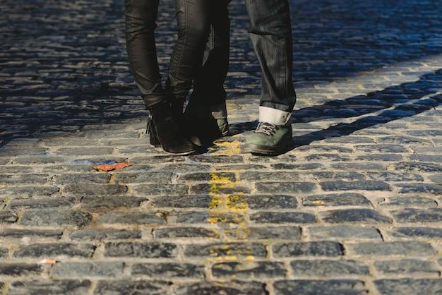 Casal apaixonado abraçado em uma cena urbana, metade inferior da foto do corpo, pernas.