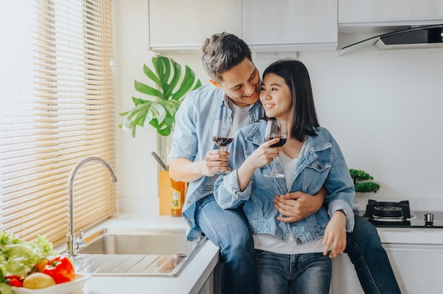 Casal apaixonado, abraçando e bebendo vinho tinto na cozinha