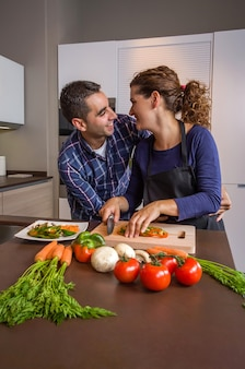 Casal apaixonado, abraçando e preparando vegetais saudáveis na cozinha. conceito moderno de estilo de vida familiar.
