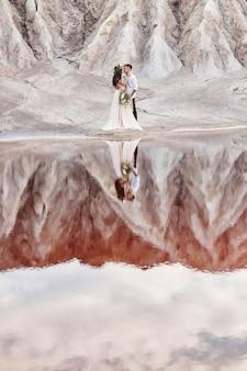 Casal apaixonado, abraçando no contexto de montanhas e lago vermelho.