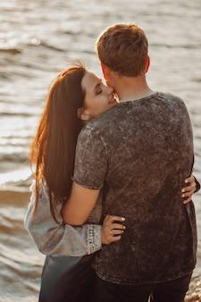 Casal apaixonado abraços à beira-mar ao sol.