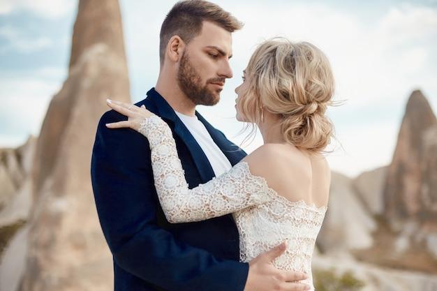 Casal apaixonado, abraços e beijos nas fabulosas montanhas na natureza. garota em um vestido longo branco com buquê de flores nas mãos dela, homem de casaco. casamento na natureza, relacionamentos e amor