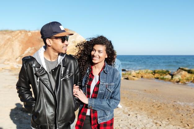 Casal apaixonado africano caminhando ao ar livre na praia