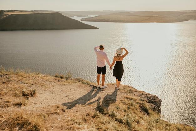 Casal apaixonado anda em uma montanha acima de um grande lago à beira-mar ao pôr do sol.