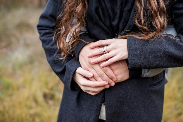 Casal apaixonado andando no parque outono segurando as mãos olhando por do sol