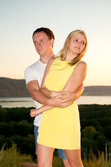Casal apaixonado ao pôr do sol no verão jovem e mulher na natureza