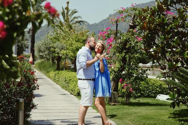 Casal apaixonado, aproveitando a lua de mel em um hotel de luxo, caminhando por jardins com palmeiras e flores de beleza. amantes felizes em uma viagem romântica se divertem nas férias de verão. romance e relaxamento de conceito