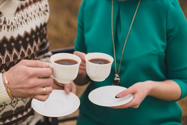 Casal apaixonado aquece e segura duas xícaras de chá na natureza