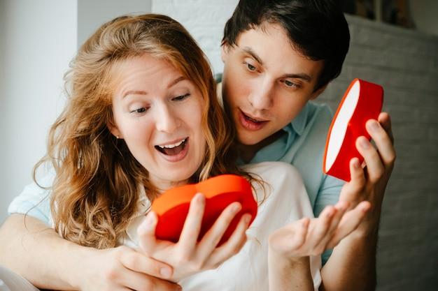 Casal apaixonado assiste a uma caixa de coração de presente no feriado do dia dos namorados.