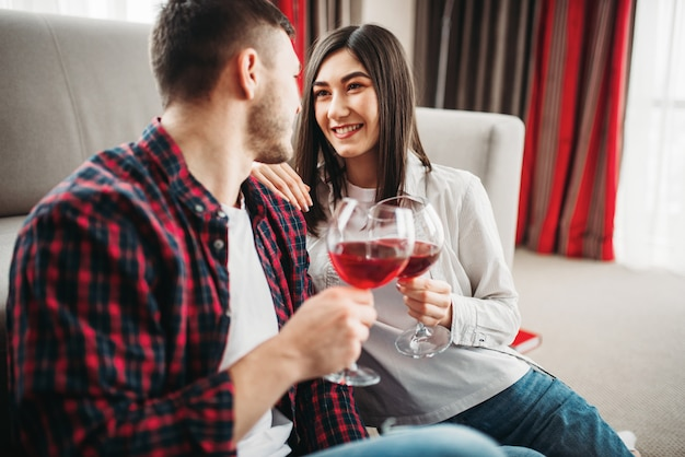 Casal apaixonado assiste filme e bebe vinho tinto