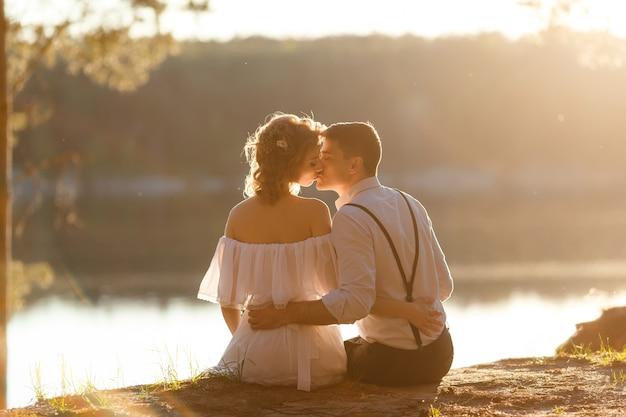 Casal apaixonado beijando ao pôr do sol