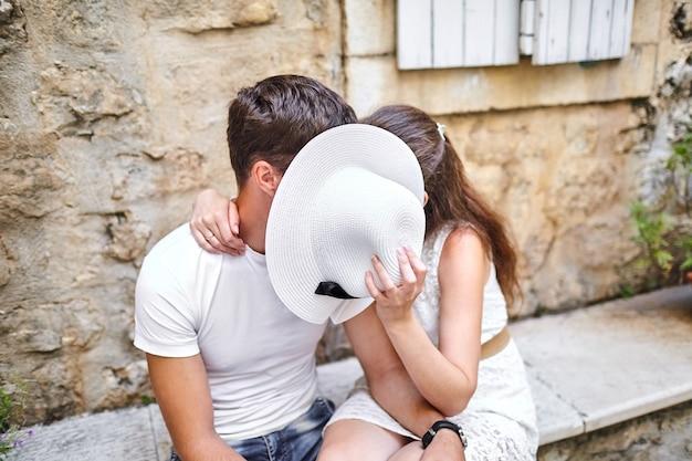 Casal apaixonado beijando atrás de um chapéu branco feminino no banco de pedra na cidade velha. jovem e mulher se abraçando. dia ensolarado de verão