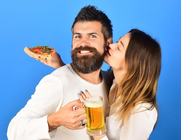 Casal apaixonado beijando e comendo pizza linda jovem de camisa branca segurando uma fatia de pizza gostosa e