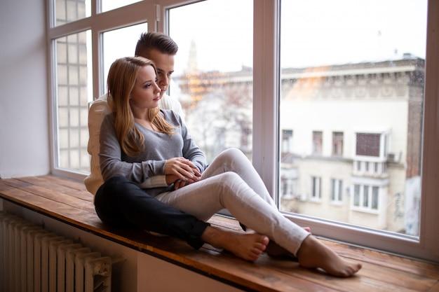 Casal apaixonado beijando e se diverte no quarto perto da janela