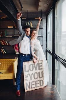 Casal apaixonado beijando segurando placa