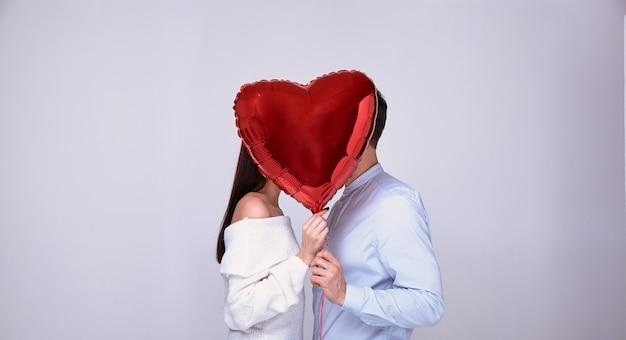 Casal apaixonado beijos se escondendo atrás de uma bola vermelha em forma de um coração.