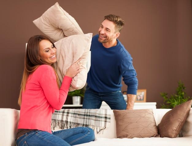 Casal apaixonado brigando de travesseiro em casa