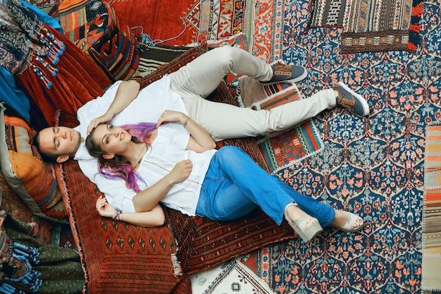 Casal apaixonado caminha e se abraça no mercado de tapetes do leste. um homem e uma mulher escolhem um tapete turco