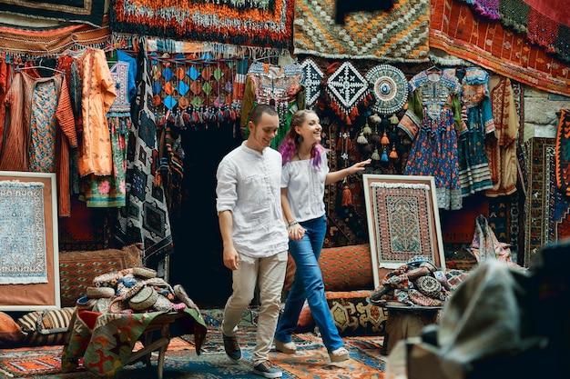 Casal apaixonado caminha e se abraça no mercado de tapetes oriental. um homem e uma mulher escolhem um tapete turco
