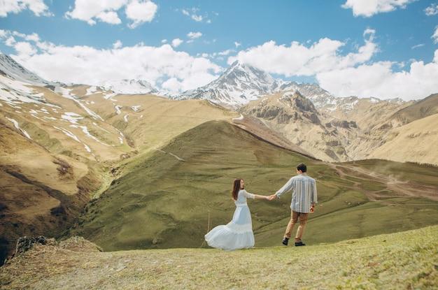 Casal apaixonado caminha no fundo de altas montanhas com geleiras no pico