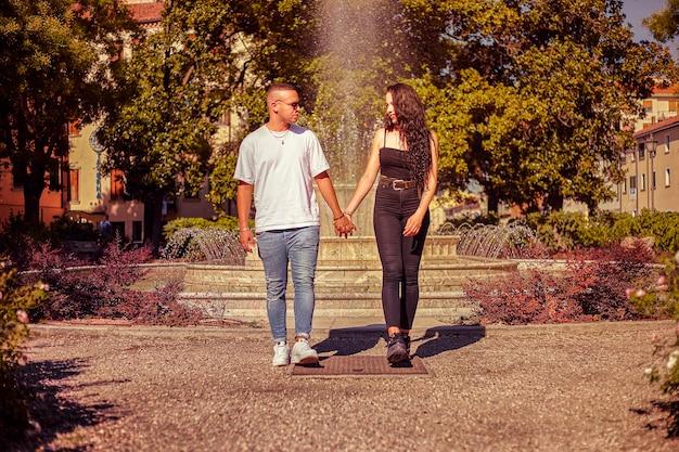 Casal apaixonado caminhando de mãos dadas em um parque ao pôr do sol