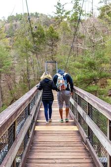 Casal apaixonado caminhando em uma ponte pênsil de madeira na floresta