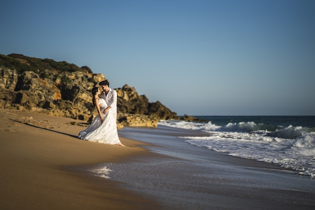 Casal apaixonado, caucasiano, feliz, vestido de branco, se abraçando na praia durante uma sessão de fotos de casamento