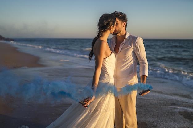 Casal apaixonado, caucasiano, segurando uma fumaça de cor azul e se beijando na praia durante um casamento