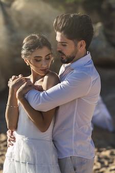 Casal apaixonado, caucasiano, vestindo roupas brancas e se abraçando na praia durante uma sessão de fotos de casamento
