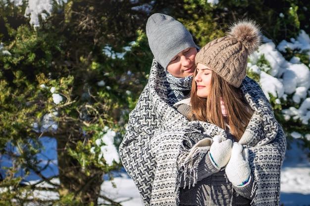 Casal apaixonado coberto com abraços cobertores na floresta de inverno