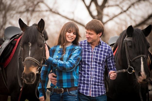Casal apaixonado com cavalos no rancho em um dia nublado outono.