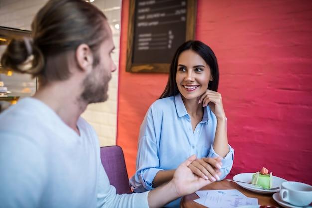 Casal apaixonado com convites de casamento em um café