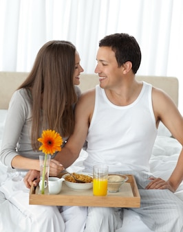 Casal apaixonado com o café da manhã sentado na cama