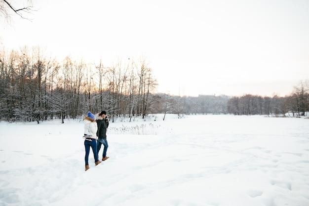 Casal apaixonado com patins vai patinar em uma pista de gelo. dia de inverno nevado.