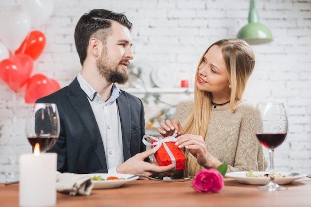 Casal apaixonado com presente no jantar romântico