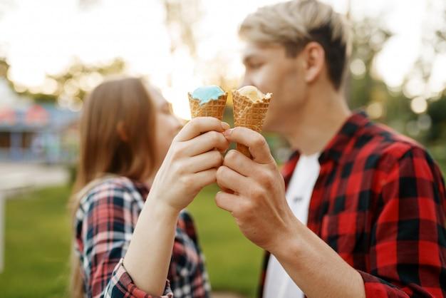 Casal apaixonado com sorvete no parque de verão