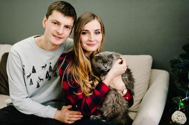 Casal apaixonado, com um gato, posando no sofá