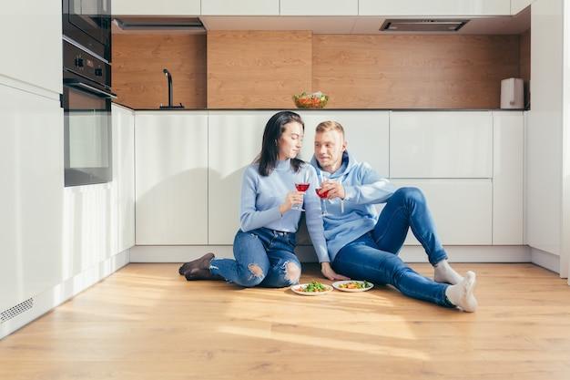 Casal apaixonado comendo uma salada de legumes, sentado no chão da cozinha e bebendo vinho