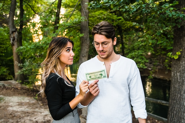 Casal apaixonado compartilha uma nota de dinheiro